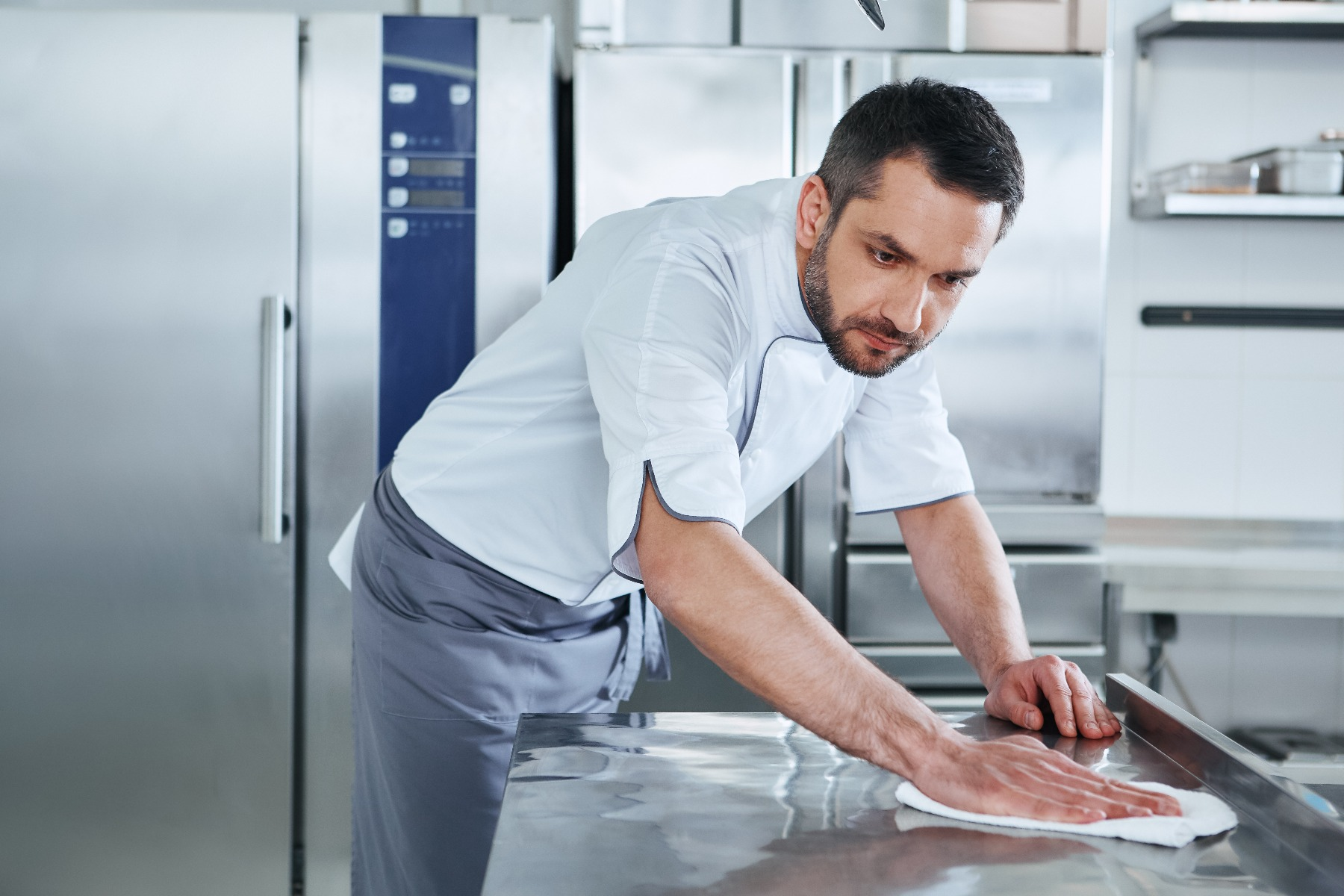 Chef wiping down Stainless Steel table in Commercial Kitchen